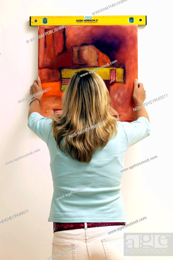 Stock Photo: Rear view of a young woman hanging a painting on a wall.