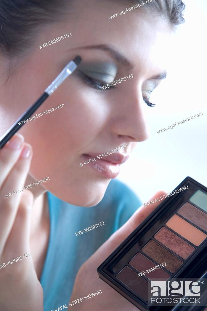 Stock Photo: woman putting eye shadow.