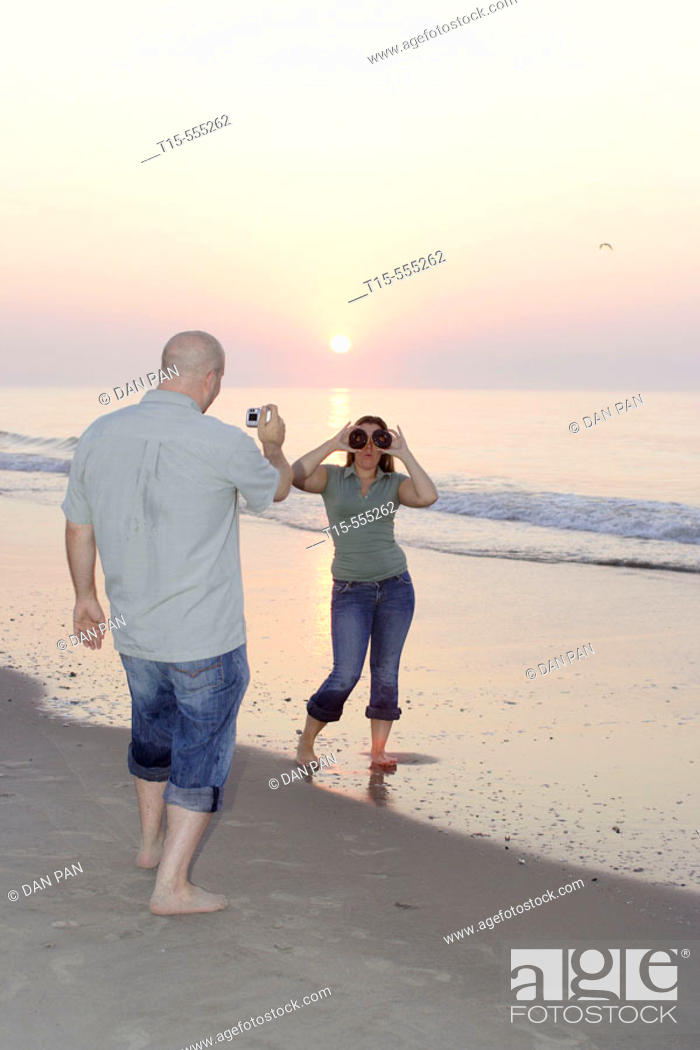 Stock Photo: Couple in their 20's having fun on the beach of ocean city taking pictures during sunrise/sunset, she plays with donuts as glasses.