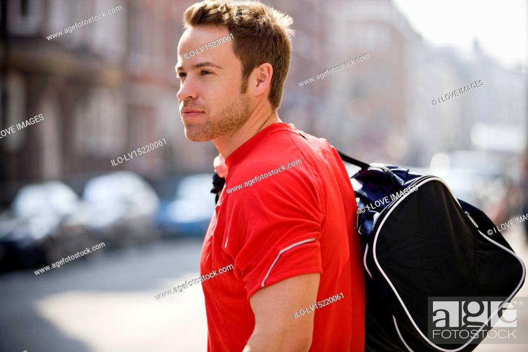 Stock Photo: A young man carrying a sports bag, walking down the street.