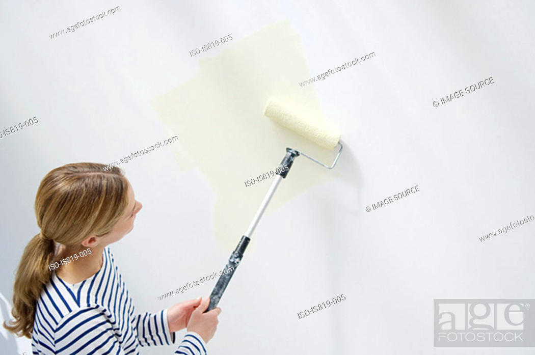 Stock Photo: Woman painting a wall.
