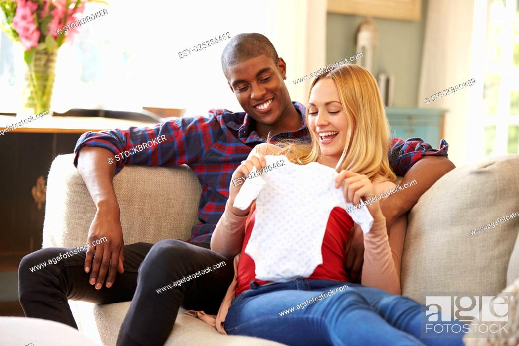 Stock Photo: Pregnant Couple On Sofa At Home Looking At Baby Clothes.