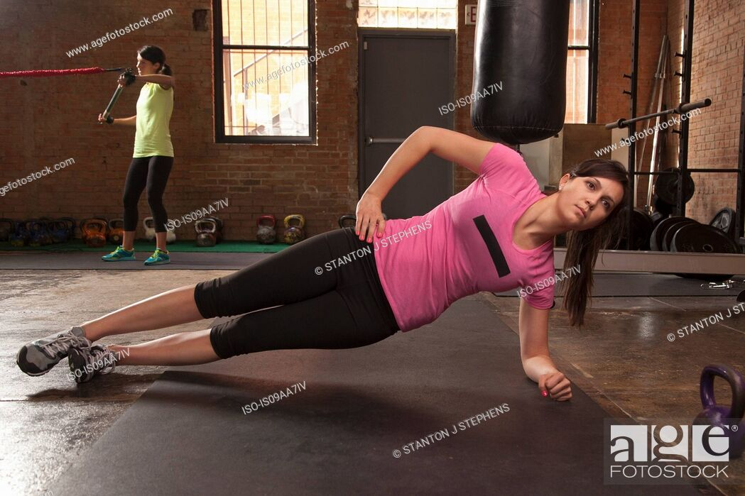 Stock Photo: Young woman exercising on mat in gym.