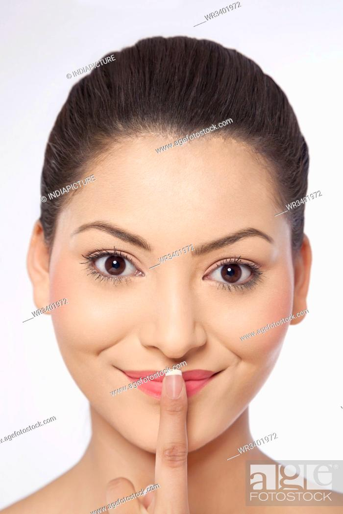 Stock Photo: Close-up of a young woman with her finger on lips.