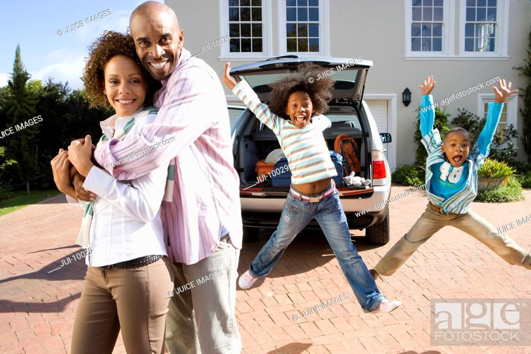 Stock Photo: Man and woman embracing in dirveway, son and daughter 6-10 jumping in background, smiling, portrait.