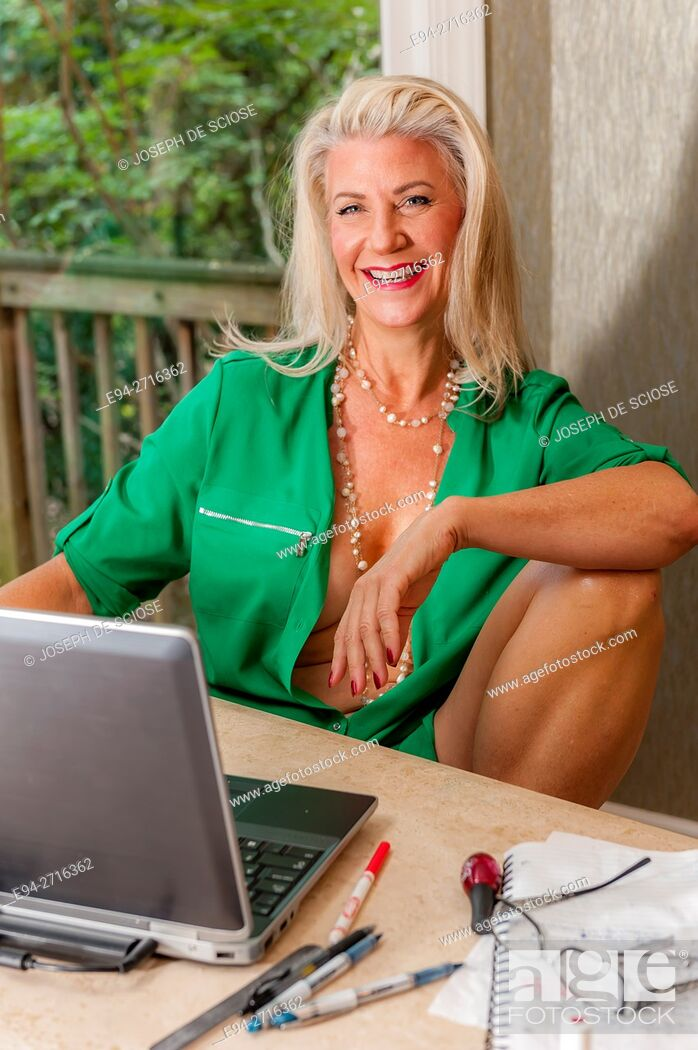 Mature women smiling nude A Partially Nude And Pretty 52 Year Old Blond Woman Sitting At A Table With Laptop Computer Stock Photo Picture And Rights Managed Image Pic E94 2716362 Agefotostock