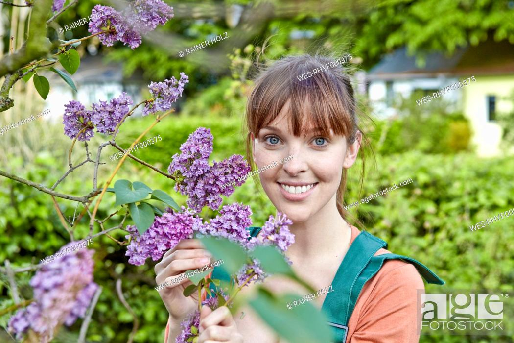 Stock Photo: Germany, Cologne, Portrait of young woman holding lilac flowers, smiling.