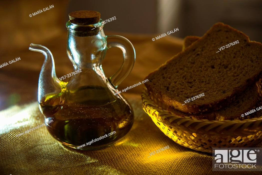 Stock Photo: Still life: oil bottle and bread in a basket. Close view.