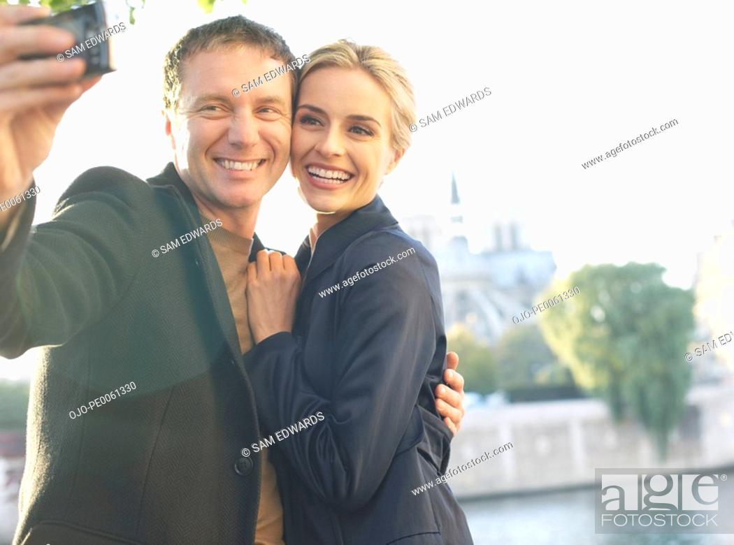 Stock Photo: Couple outdoors taking self-portrait using digital camera smiling.