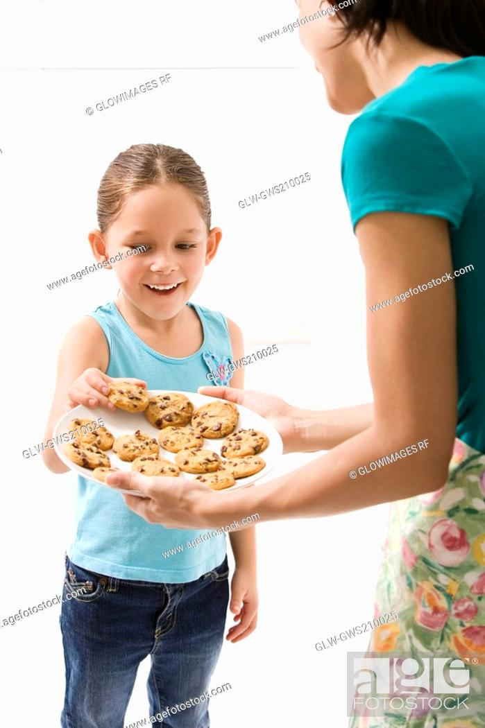 Stock Photo: Close-up of a young woman serving cookies to her daughter.