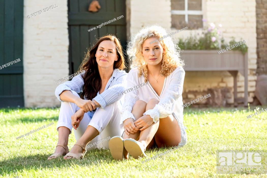 Stock Photo: Two women sitting in the garden on grass in the sunshine.