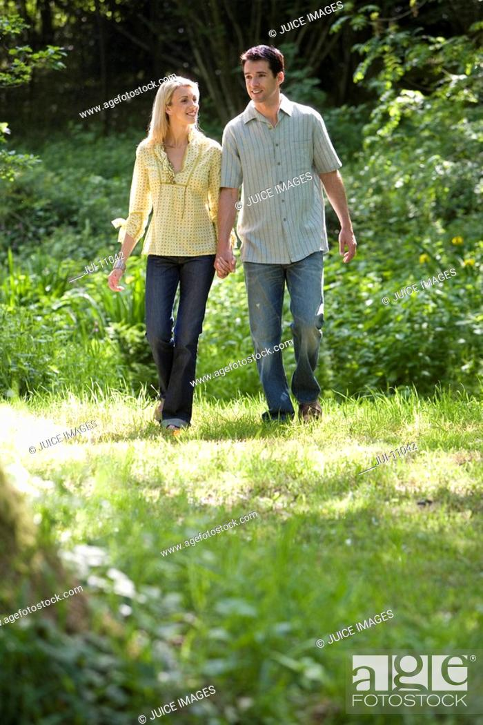 Stock Photo: Young couple hand in hand in forest, low angle view.