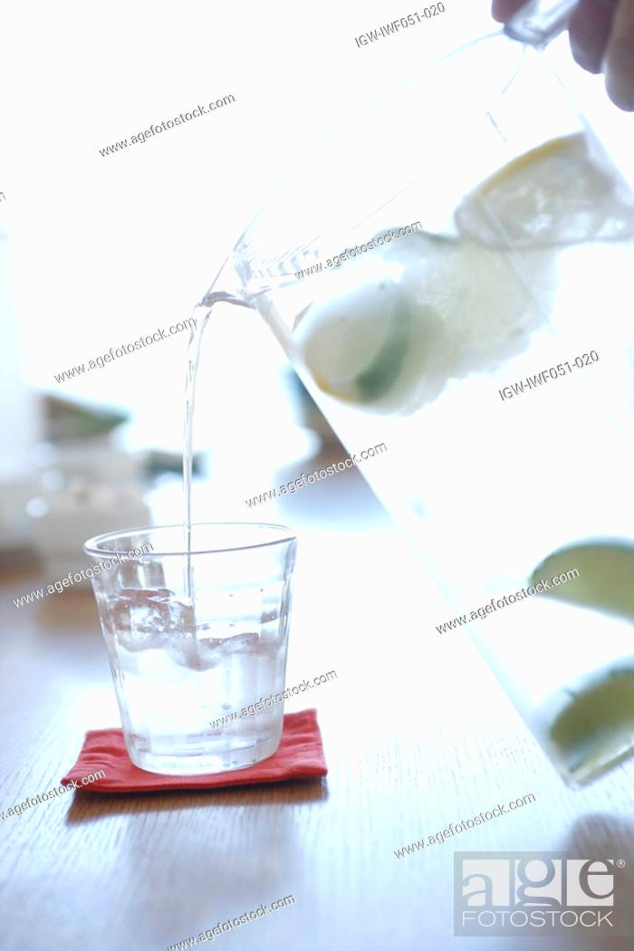 Stock Photo: Person pouring water in glass, close-up.