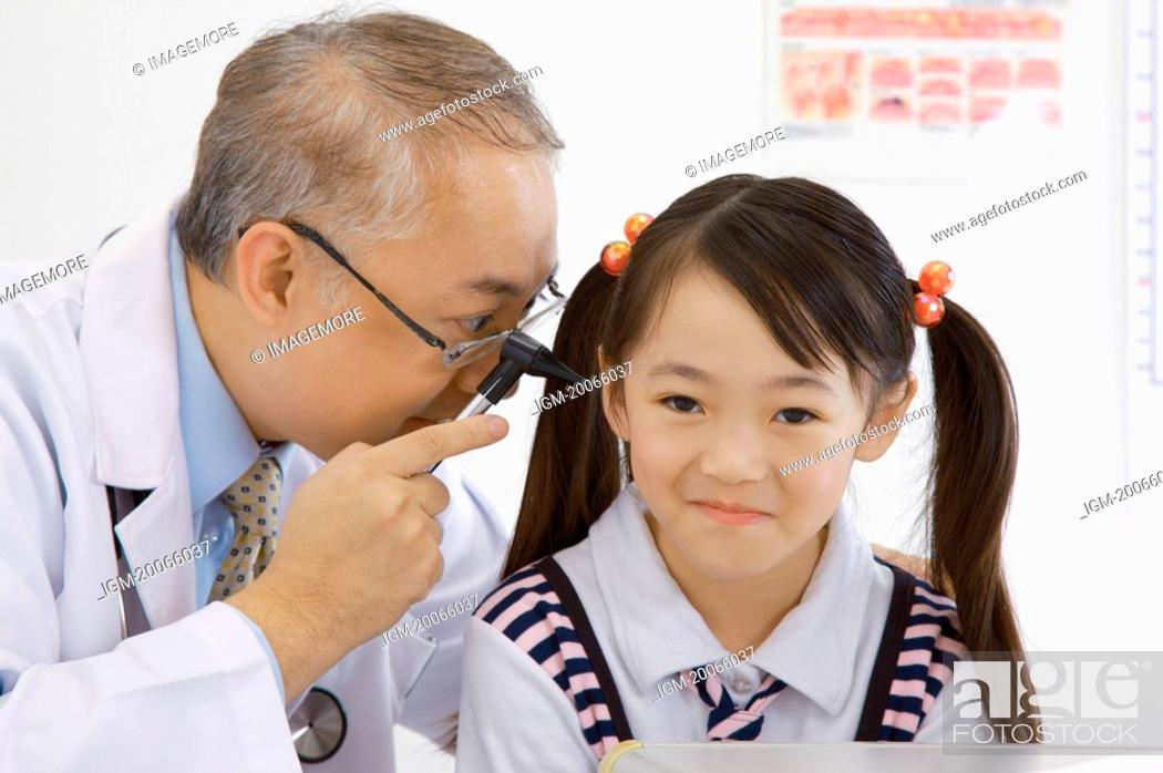Stock Photo: Doctor checking little girl's ear with medical equipment.
