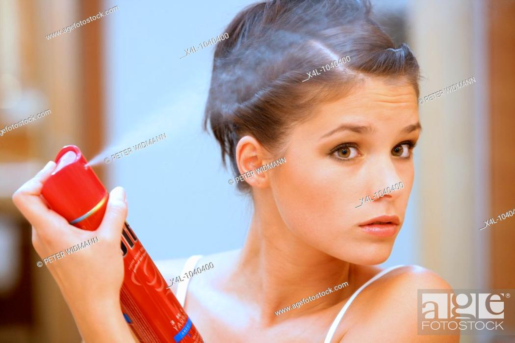Stock Photo: young woman using hairspray.