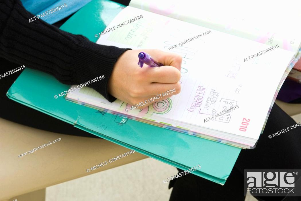 Stock Photo: Student writing in notebook.