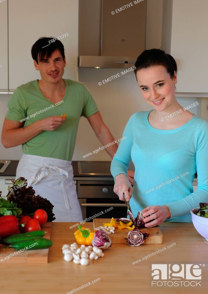 Imagen: Young couple in kitchen preparing salad.