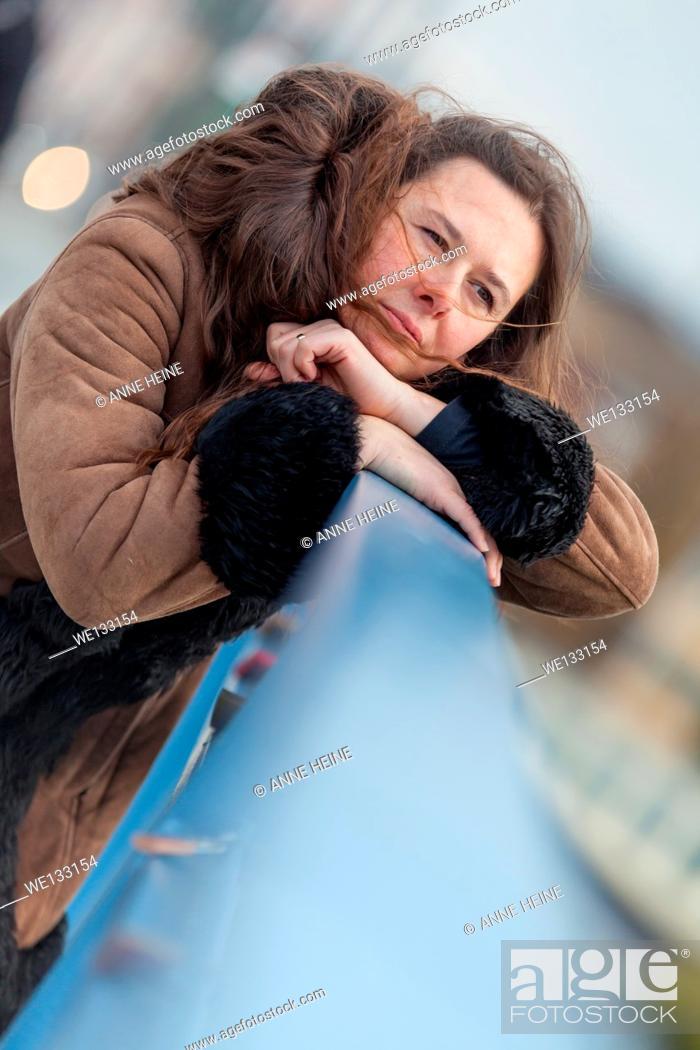 Stock Photo: Woman waiting on bridge looking into distance, leaning head on hand, bridge, Bonn, Germany.