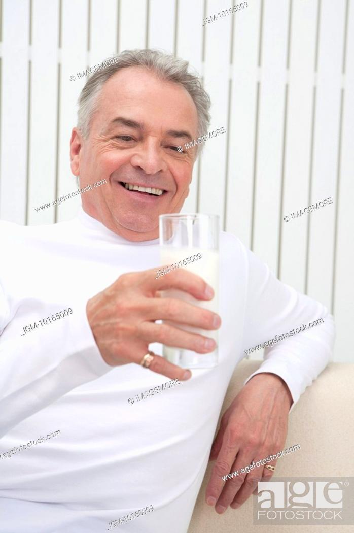 Stock Photo: Domestic Life, a Senior-aged man holding a glass of drink and smiling.
