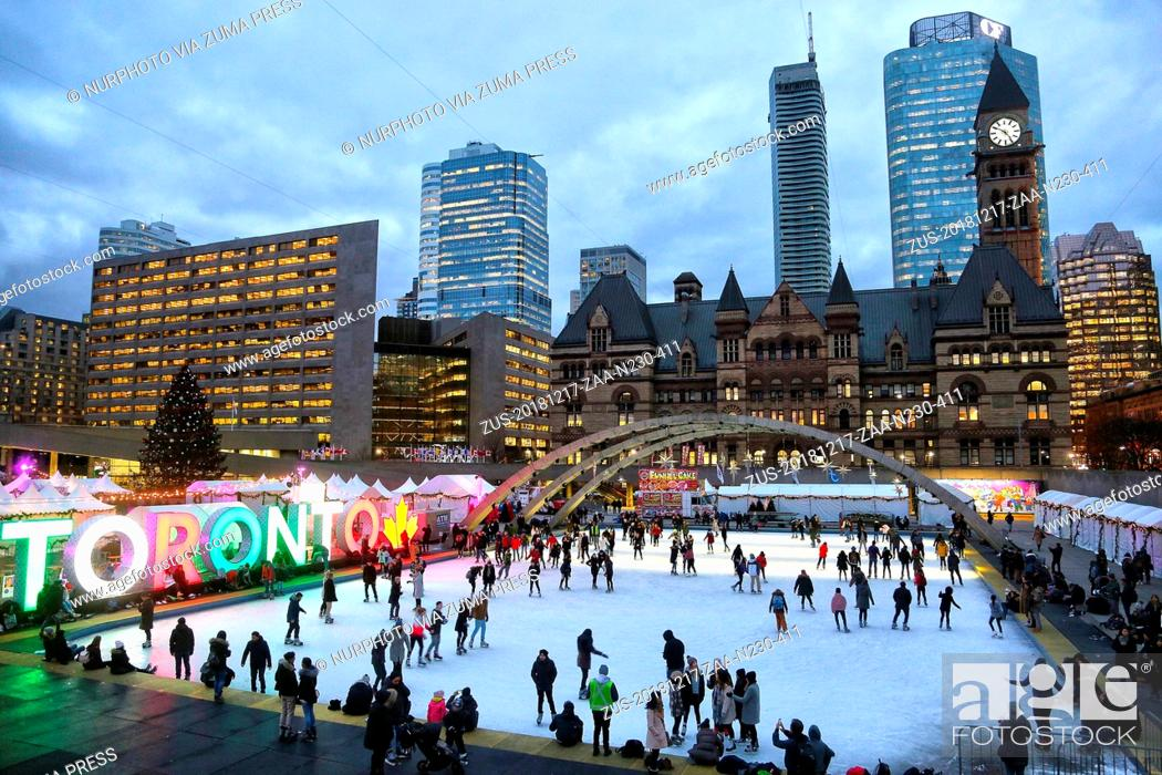 Photo de stock: December 17, 2018 - Toronto, Ontario, Canada - People enjoy ice skating at an outdoor ice rink in Nathan Phillips Square in downtown Toronto, Ontario, Canada.