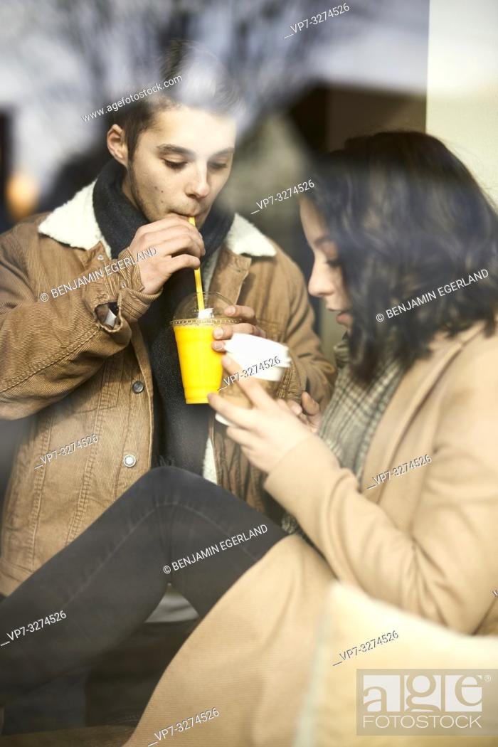 Stock Photo: young teenage couple drinking takeaway orange juice and take-away coffee behind window in café, plastic cup and drinking straw, in Cottbus, Brandenburg, Germany.