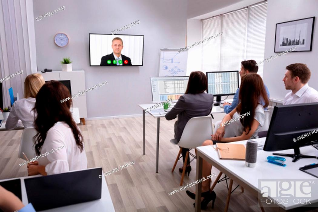 Stock Photo: Rear View Of A Business People Looking At Screen During Video Conference In Office.