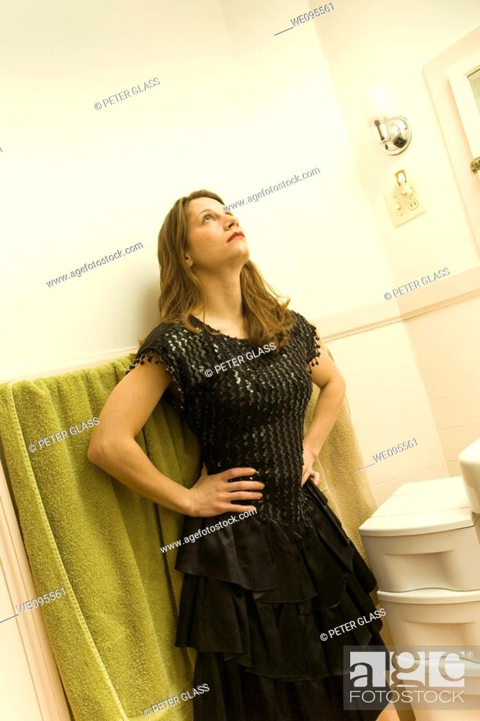 Stock Photo: Young woman, in an evening dress, standing in her bathroom.