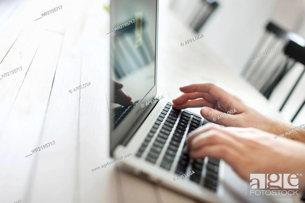 Stock Photo: Cropped hands using laptop at cafe table.