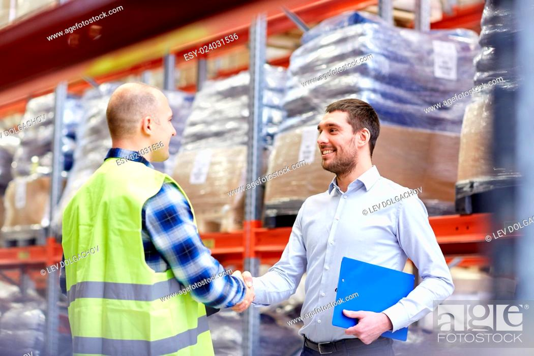 Stock Photo: wholesale, logistic, people and export concept - manual worker and businessmen with clipboard shaking hands and making deal at warehouse.