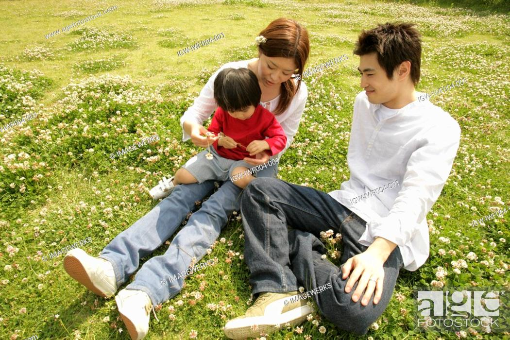 Stock Photo: A family relaxing in a garden full of flowers.