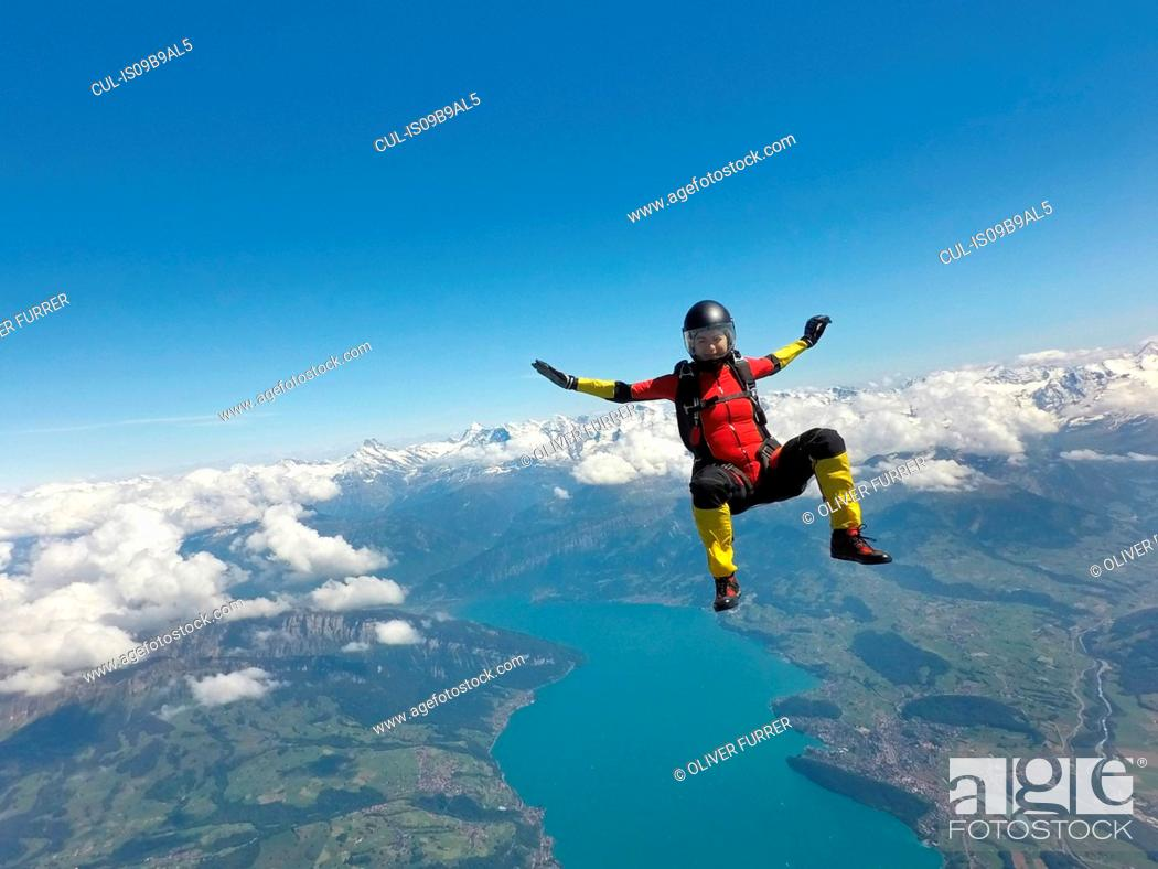 Stock Photo: Female skydiver sitting up in free fall above clouds and lake.