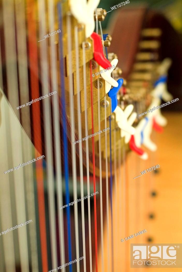 Stock Photo: Strings lined up in a row and tightly stretched on a harp.