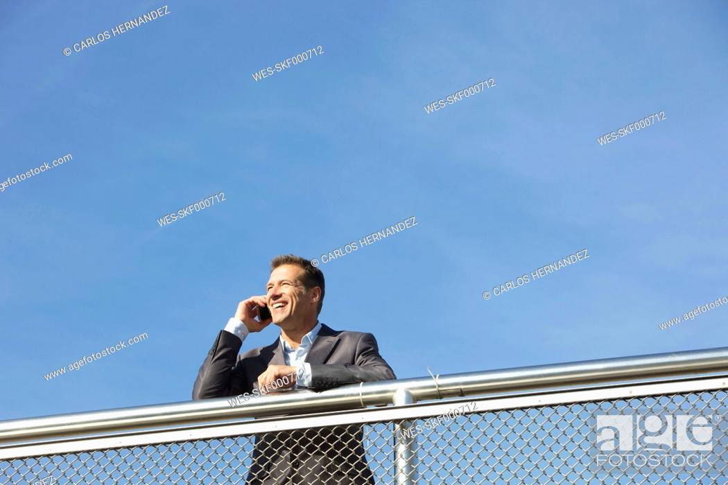 Stock Photo: Germany, Bavaria, Munich, Businessman talking on cell phone, smiling.