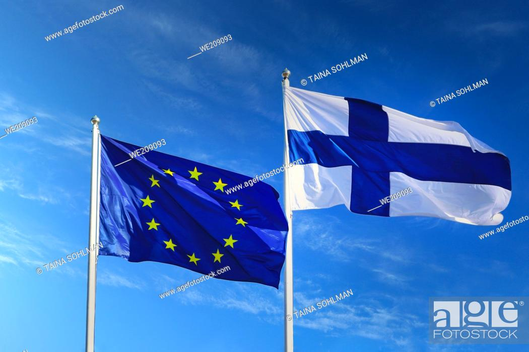 Stock Photo: Flags of EU and Finland against blue sky with white clouds on Europe Day May 9, 2020.