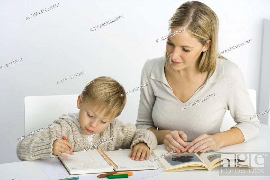 Stock Photo: Mother and son sitting at table, boy coloring.