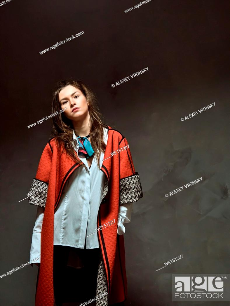 Stock Photo: Young girls having fun in the Studio. They are trendy long shirts and coats. The collection of clothes is provided by a known fashion designer from Belarus.