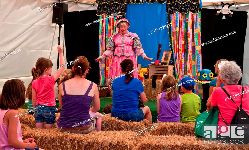 Stock Photo: This mature older woman is telling nursey rhymes to children sitting on hay bales, as she portrays Mother Goose  Event took place on July 14, 2010 in Albany.