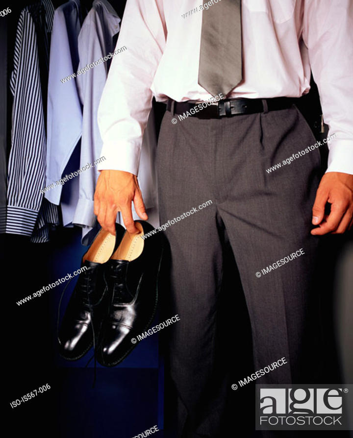 Stock Photo: Man holding a pair of shoes.