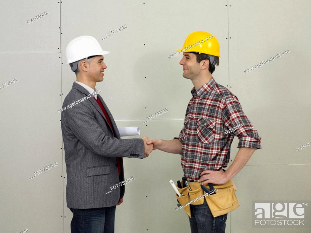 Stock Photo: An architect shaking hands with a construction worker.