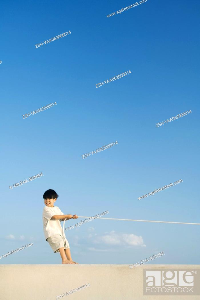 Stock Photo: Little boy playing tug-of-war, smiling at camera, mid-distance.