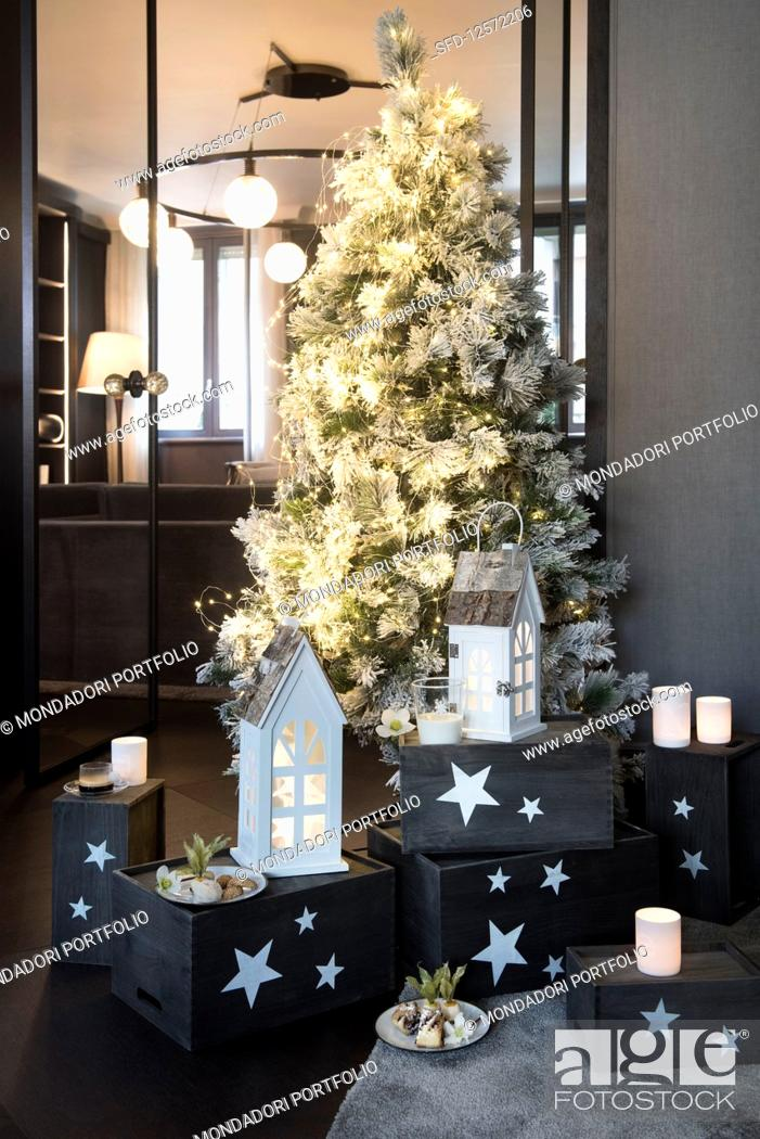 Photo de stock: Christmas tree decorated in white amongst tealight holders and lanterns on grey wooden boxes.