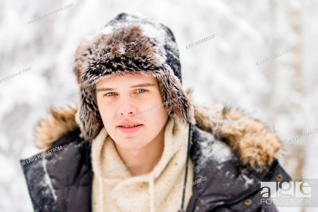 Stock Photo: Christmas scene with natural looking teenage male outdoors in snow covered winter landscape.