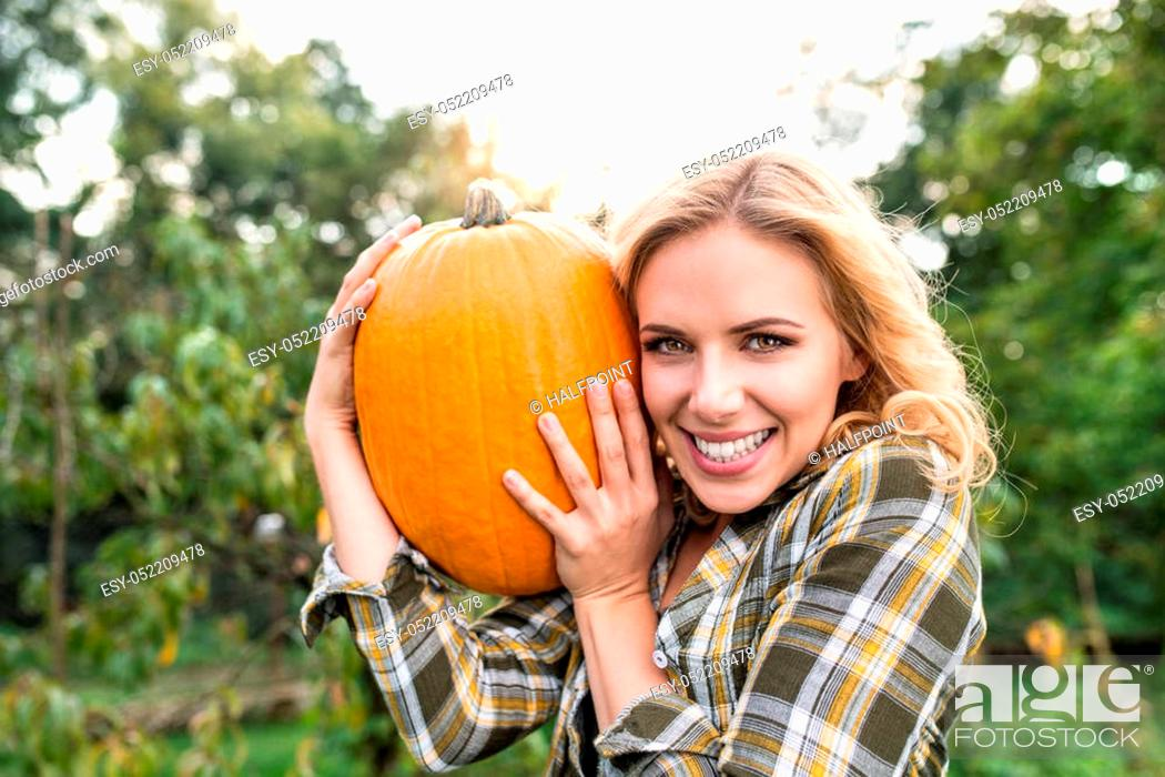 Stock Photo: Beautiful young blond woman in checked shirt working in her garden harvesting pumpkins. Autumn nature.