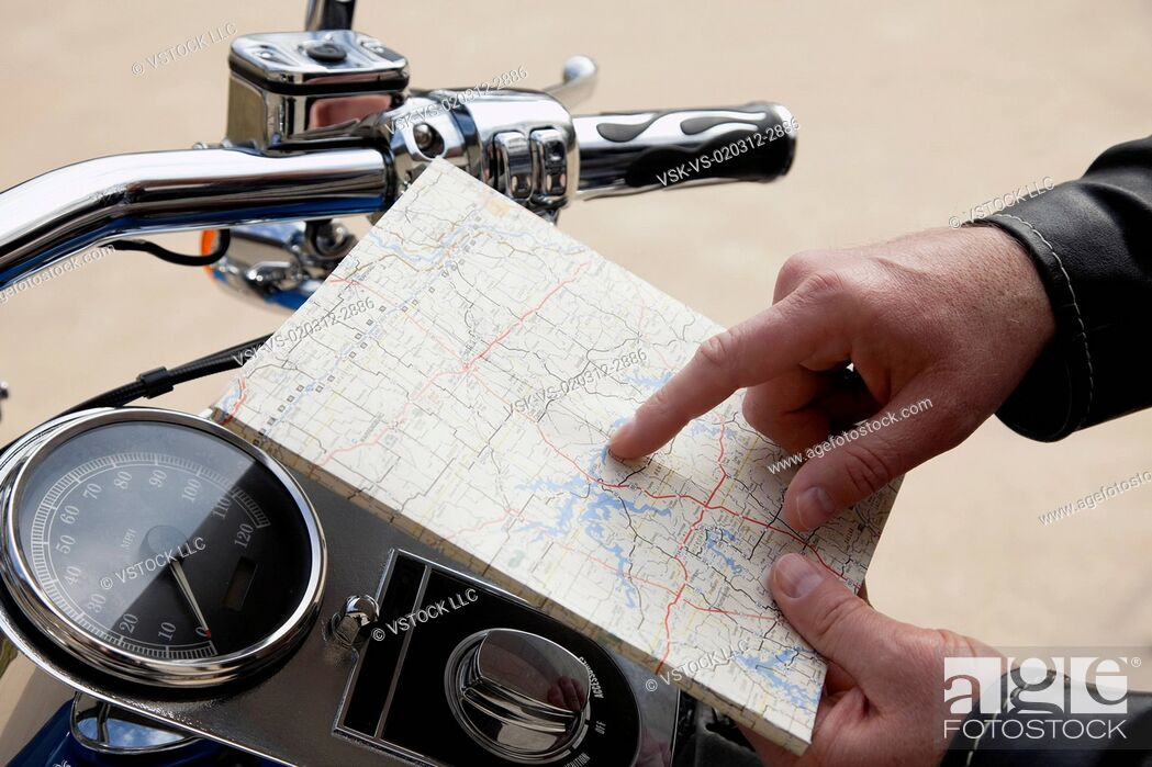 Stock Photo: USA, Illinois, Metamora, Close up of man's hand holding map near motorcycle handlebars.