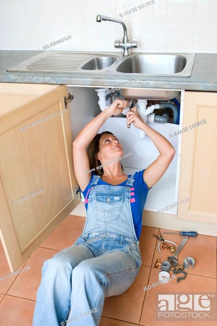 Stock Photo: A young woman repairing a sink.