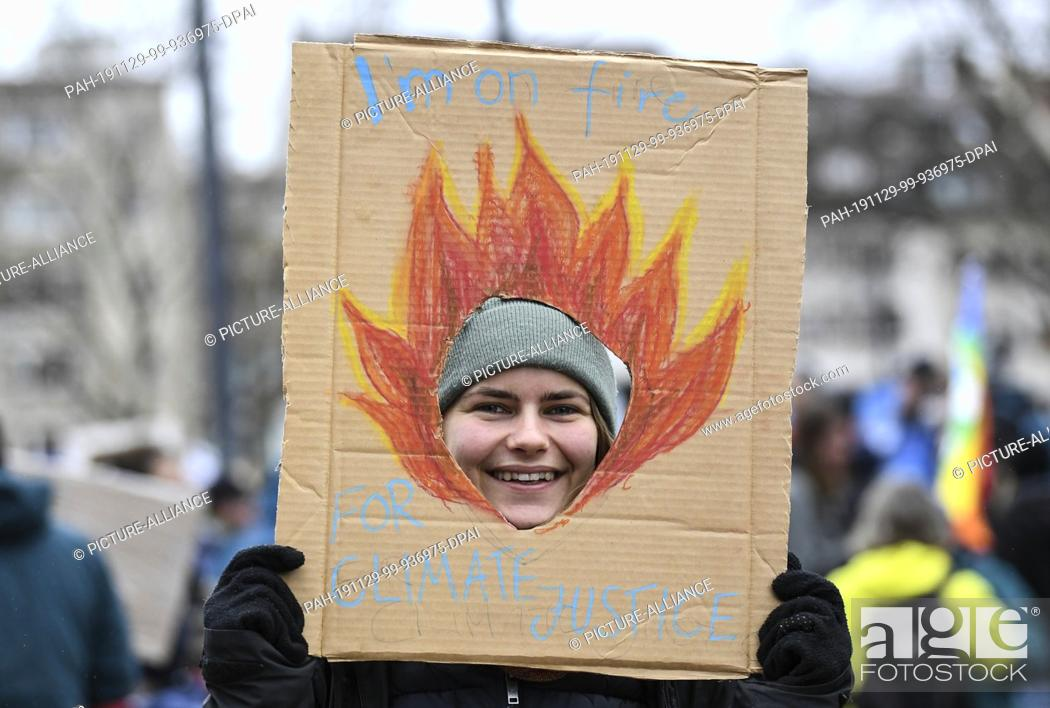 "Stock Photo: 29 November 2019, Baden-Wuerttemberg, Freiburg: At the action day of """"Fridays for Future"""" a schoolgirl holds a poster with the inscription """"I'm on fire for."