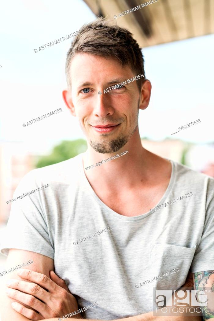 Stock Photo: Portrait of confident man standing arms crossed.