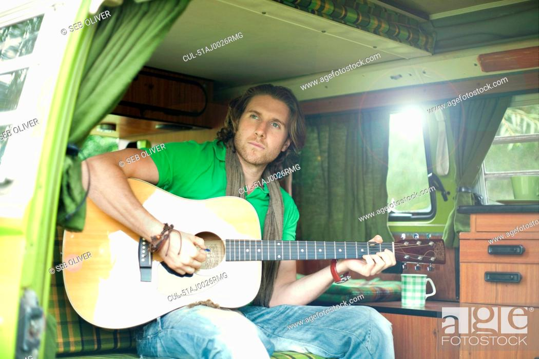Stock Photo: Man playing guitar in trailer.