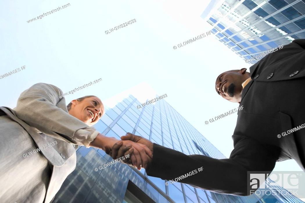 Stock Photo: Low angle view of a businessman and a businesswoman shaking hands.