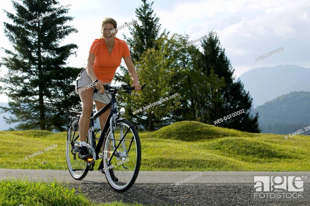 Stock Photo: Germany, Bavaria, Mittenwald, Woman with mountainbike, smiling.